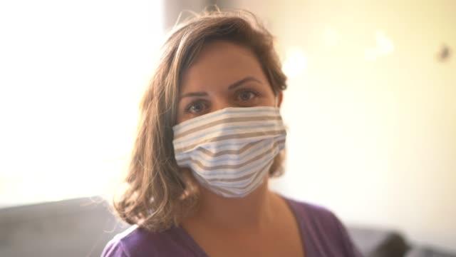 vídeos de stock, filmes e b-roll de retrato de uma mulher usando máscara facial em casa - cabelo louro