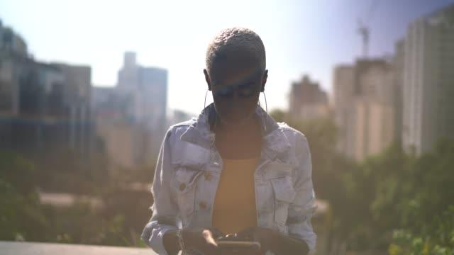 portrait of a woman walking in a city using smartphone - pardo brazilian stock videos & royalty-free footage