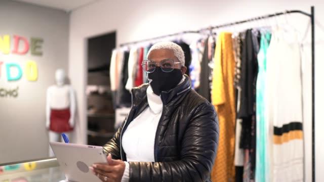 porträt einer frau, die gesichtsmaske trägt und digitales tablet benutzt, das in einem schuhgeschäft arbeitet - 40 seconds or greater stock-videos und b-roll-filmmaterial