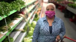 Portrait of a woman with disposable medical mask shopping in supermarket