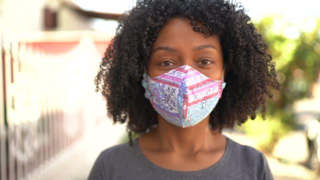 porträtt av en kvinna med ansiktsmask på gatan - ansvar bildbanksvideor och videomaterial från bakom kulisserna