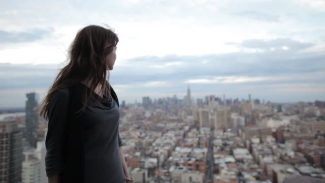 vídeos de stock e filmes b-roll de portrait of a woman woman on a rooftop overlooking manhattan - horizon