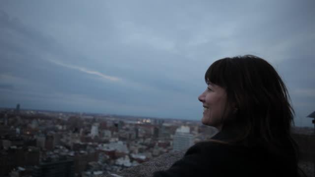 vídeos de stock, filmes e b-roll de portrait of a woman woman on a rooftop overlooking manhattan - horizonte