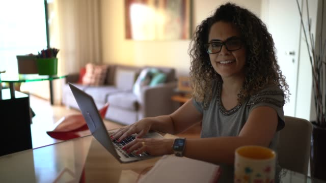 portrait of a woman working from home using laptop - satisfaction stock videos & royalty-free footage