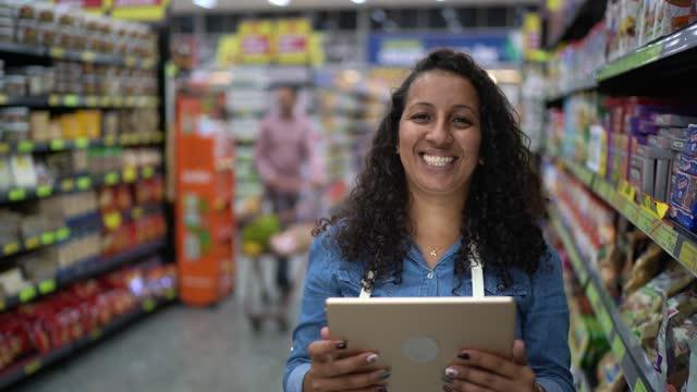 vidéos et rushes de verticale d'une femme travaillant dans un supermarché utilisant la tablette numérique - qualité