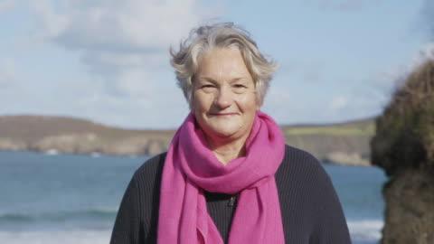 porträtt av en kvinna som ler till kamera med ett hav och kustlinje bakom henne. - 50 54 år bildbanksvideor och videomaterial från bakom kulisserna