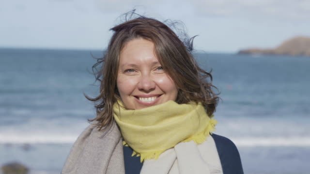 portrait of a women smiling to camera with a sea and coastline behind her. - 50 59 years stock videos & royalty-free footage