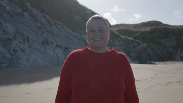 portrait of a women standing on a coastal path smiling to camera. - real people stock videos & royalty-free footage