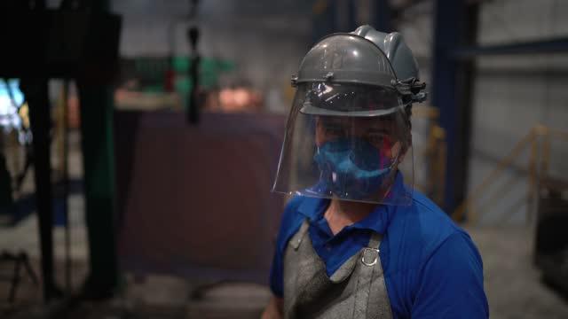 portrait of a worker wearing welding helmet in a metal industry - metalwork stock videos & royalty-free footage
