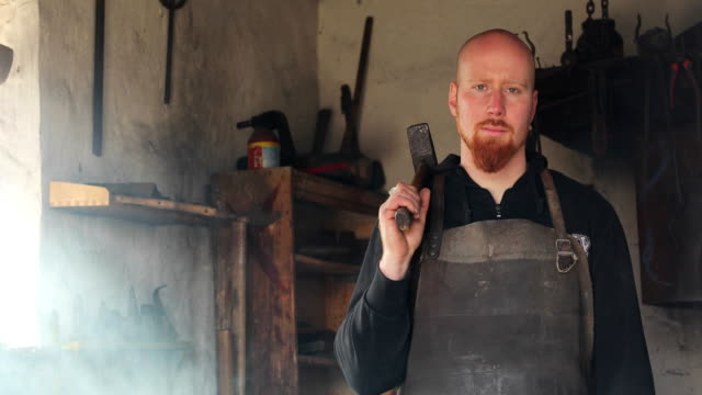 vídeos de stock e filmes b-roll de portrait of a young adult blacksmith in his forge - careca