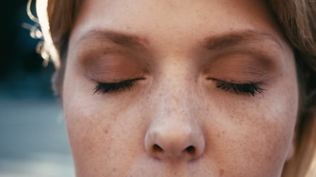 portrait of a young adult woman at sunset, opening and closing her blue eyes - freckle stock videos & royalty-free footage