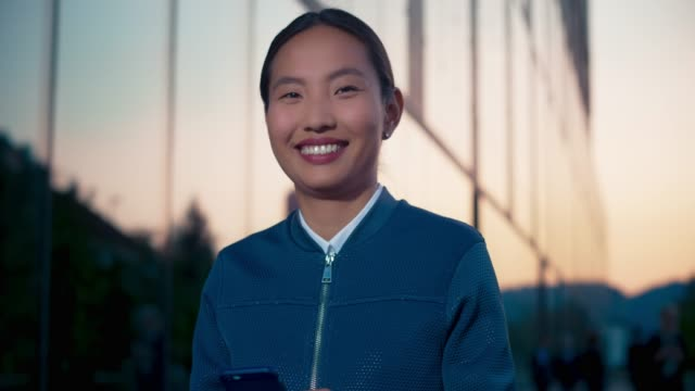 portrait of a young asian female entrepreneur typing on her smartphone outside a modern business building and smiling into the camera - focus on foreground stock videos & royalty-free footage