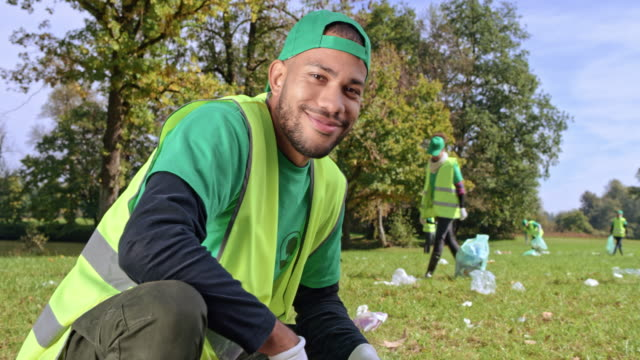 portrait of a young biracial man picking up litter with the local clean up team - bin bag stock videos & royalty-free footage