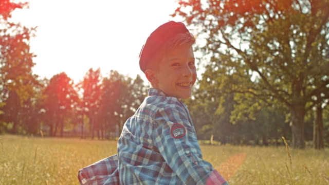 slo mo ts portrait of a young boy running across meadow in sunshine - boys stock videos & royalty-free footage