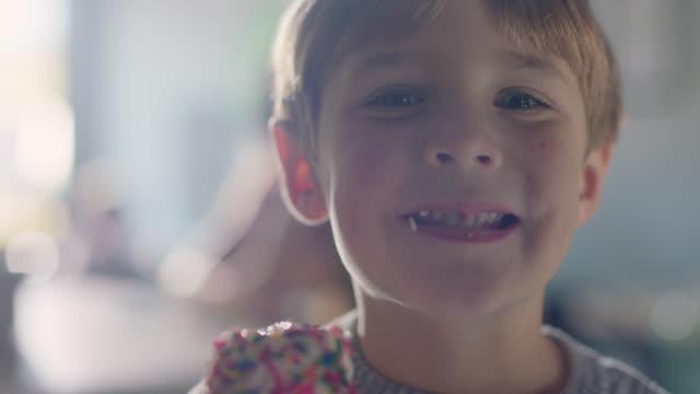 vídeos y material grabado en eventos de stock de slo mo. cu. portrait of a young boy smiles while eating a vanilla ice cream cone - helado de vainilla
