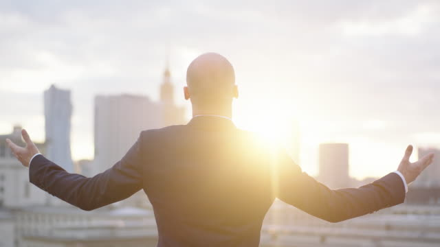 Portrait of a young businessman. Opening arms. Cityscape in the background