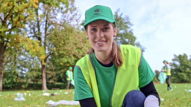 portrait of a young caucasian woman smiling while picking litter in the meadow with the local clean-up organization - environmentalist stock videos & royalty-free footage