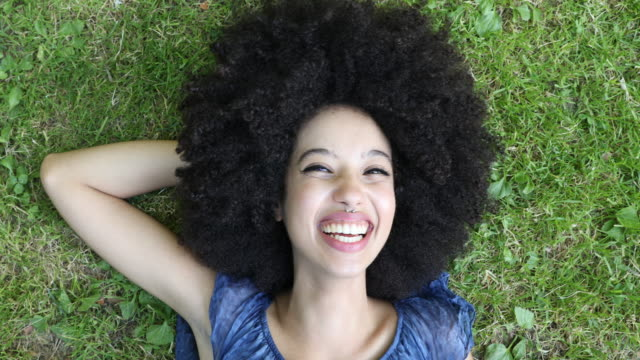 portrait of a young cheerful woman looking at camera with curly hair style - eyes closed stock videos & royalty-free footage