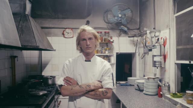 vidéos et rushes de verticale d'un jeune chef dans sa cuisine - tatouage
