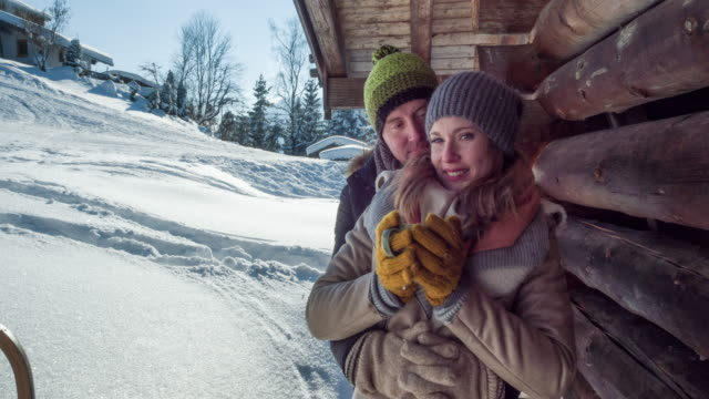 Portrait of a young couple at a log cabin in winter