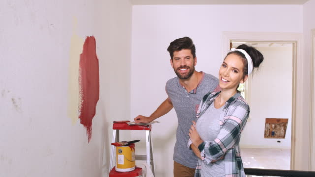 Portrait of a young couple laughing in their home during a renovation.