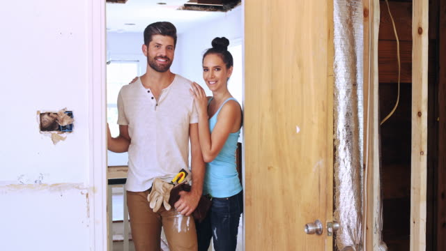Portrait of a young couple posing in their renovation project.