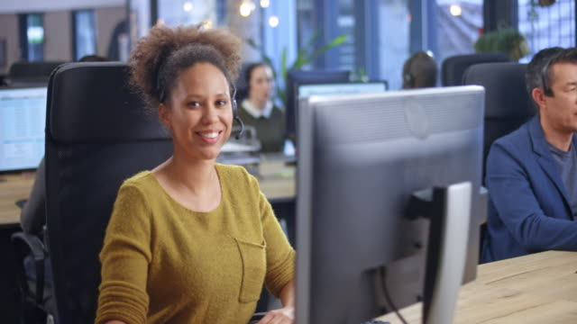 portrait of a young female call center agent smiling into the camera at her office desk - dolly shot stock videos & royalty-free footage