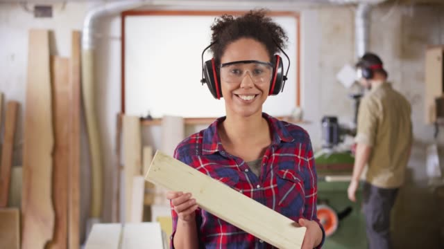 ds portrait of a young female carpenter holding a piece of wood and smiling in the workshop - timber stock videos and b-roll footage