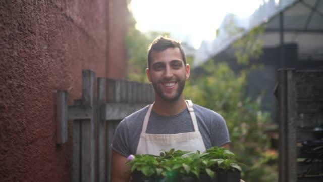 porträt eines jungen floristen, der eine kiste voller sämlinge hält - stolz stock-videos und b-roll-filmmaterial