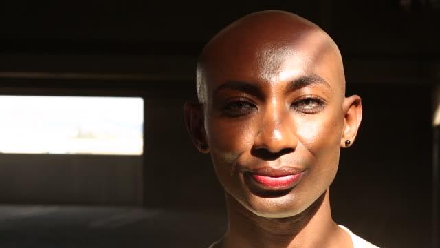vidéos et rushes de portrait of a young gay men outdoors on a sunny day. - transgenre