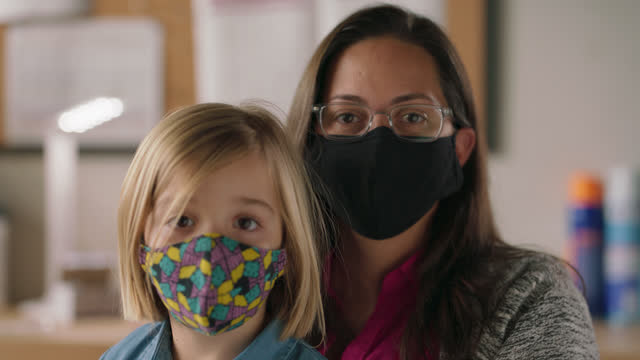 slo mo cu portrait of a young girl and her mother wearing protective face masks - alertness stock videos & royalty-free footage