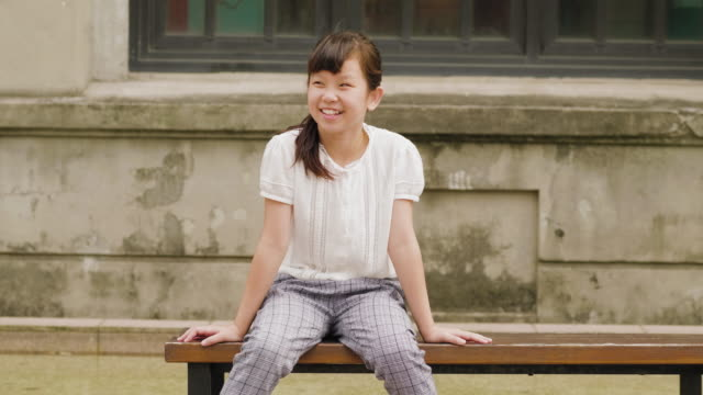 portrait of a young girl sitting on a bench in a public park in taipei - taipei stock videos & royalty-free footage