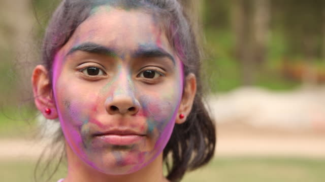 stockvideo's en b-roll-footage met portrait of a young girl smiling with colored powder on her face outside. - haar naar achteren