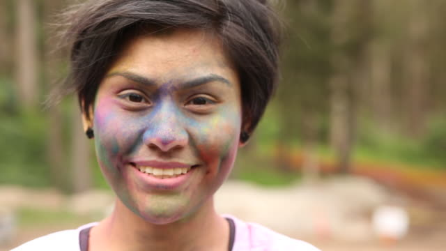 portrait of a young girl smiling with colored powder on her face outside. - nur weibliche teenager stock-videos und b-roll-filmmaterial