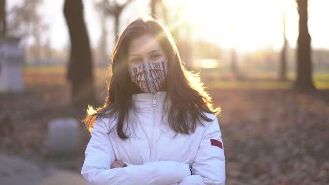 vídeos y material grabado en eventos de stock de retrato de una joven con mascarilla de pie en un parque - sólo una adolescente