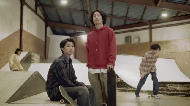 vidéos et rushes de verticale d'un jeune skateboarder masculin japonais dans le parc de patin (mouvement lent) - quatre personnes