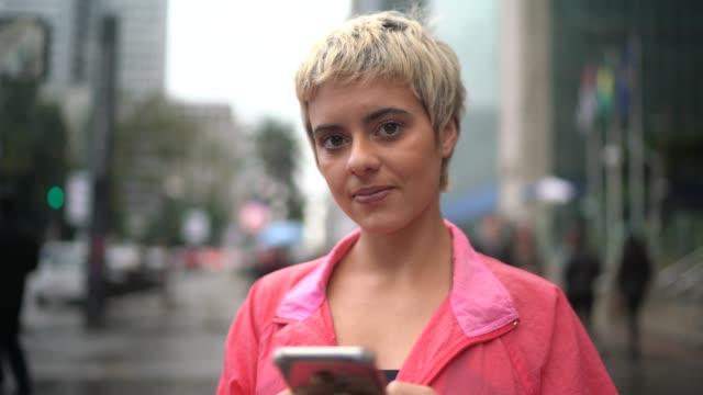 vídeos y material grabado en eventos de stock de retrato de una joven latina usando smartphone en la ciudad - agarrar