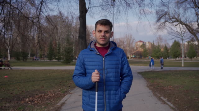 vídeos y material grabado en eventos de stock de retrato de una persona joven con discapacidad visual de pie en el parque público, sosteniendo su bastón - diversidad funcional