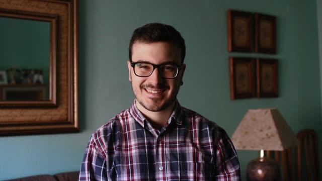 vídeos de stock e filmes b-roll de portrait of a young man at home. he is smiling - dentro