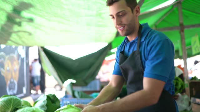 portrait of a young man checking product in street market - agricultural fair stock videos & royalty-free footage