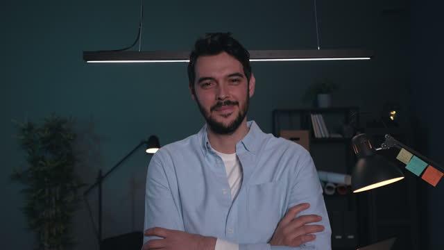 vidéos et rushes de verticale d'un entrepreneur de jeune homme tard dans la nuit à son bureau. - bras croisés