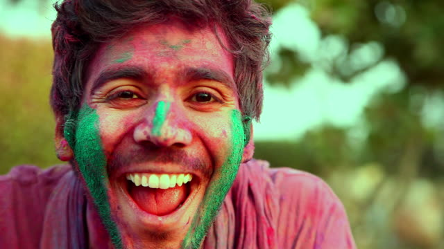 Portrait of a young man playing holi and laughing, Delhi, India