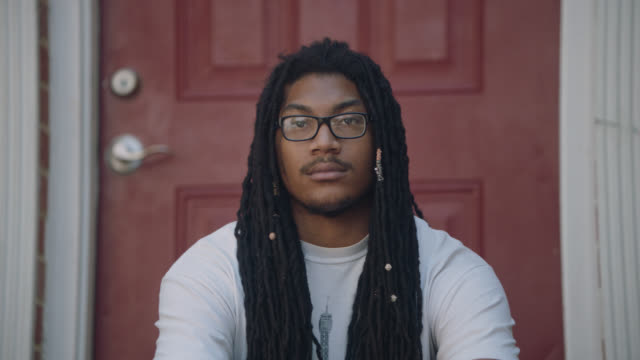 slo mo portrait of a young man sitting by his front door - african american ethnicity stock videos & royalty-free footage