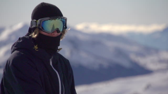 portrait of a young man snowboarder on a scenic snow covered mountain top.  - super slow motion - filmed at 240 fps - skibrille stock-videos und b-roll-filmmaterial