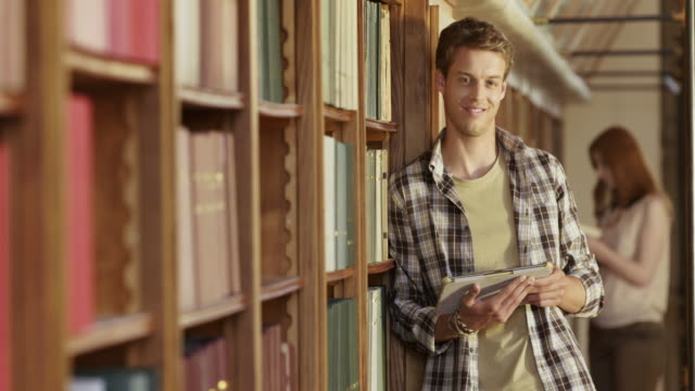 DS Portrait of a young man standing by a library bookshelf with a tablet