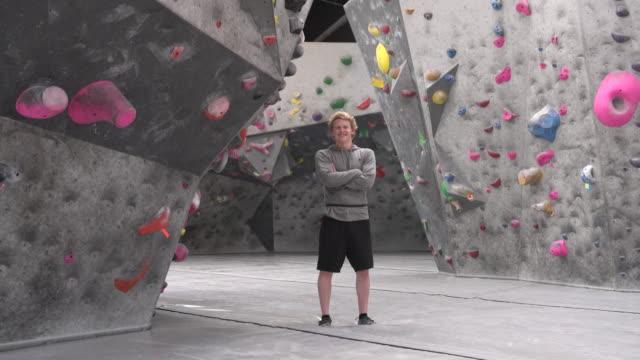 stockvideo's en b-roll-footage met ws portrait of a young man standing in front of a rock climbing wall - armen over elkaar