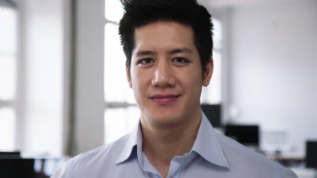 vídeos de stock e filmes b-roll de portrait of a young man standing in office - só um homem jovem