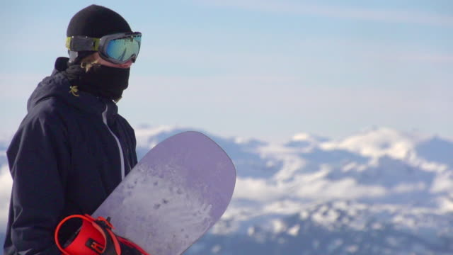 portrait of a young man standing with his snowboard on a scenic snow covered mountain top.  - slow motion - snowboarding stock videos & royalty-free footage