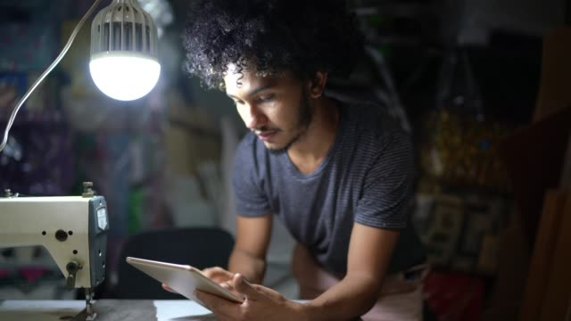 portrait of a young man using a digital tablet in upholstery workshop - pardo brazilian stock videos & royalty-free footage