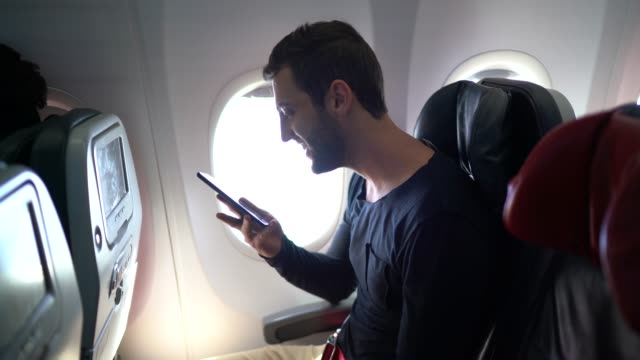 portrait of a young man using smartphone inside an airplane - one man only stock videos & royalty-free footage